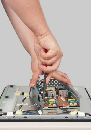 solucion de problemas: El hombre la reparación de monitor LCD fotografiado sobre un fondo blanco Foto de archivo