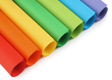 Rolls of colored construction paper isolated with shadows on white background.