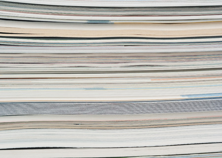 Side view of a stack of paper, books and magazines.