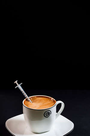 Coffee with milk on a plate with a syringe inside the coffee.This is a Portrait format photo taken on a black background under artificial light in a studio.