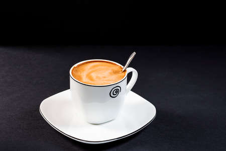 Creamy latte in a porcelain cup with saucer.Horizontal format photography taken in studio with artificial light.