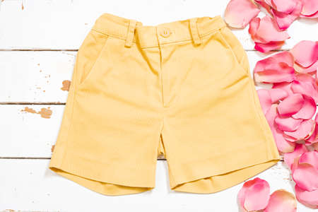 Yellow shorts on a white wood and some rose petals. The photograph is an overhead shot with a horizontal format.