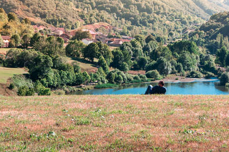 Man lying in the meadow resting on the route linking the villages of Cain and Posada de Valdeon.The photo is taken in horizontal format. Stock Photo