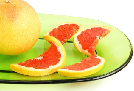 Grapefruit, whole and sliced on a green glass oval shaped plate Stock Photo