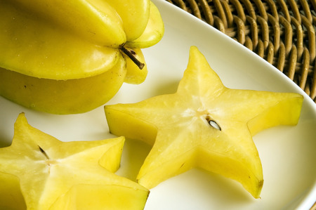 Fresh star-fruits sliced and whole on a white plate Stock Photo