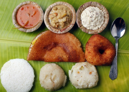 dosa: Masala dosa, idly, vada, chutney, upma, curry and sambar on a banana leaf Stock Photo