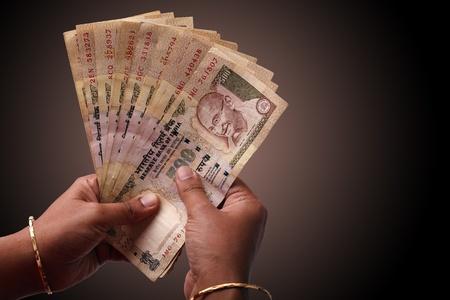 pagando: Mujer contando unos billetes de 500 rupias