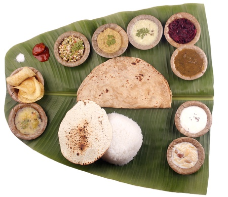 South indian lunch including rice, chapatti and curries on banana leaf with clipping mask photo
