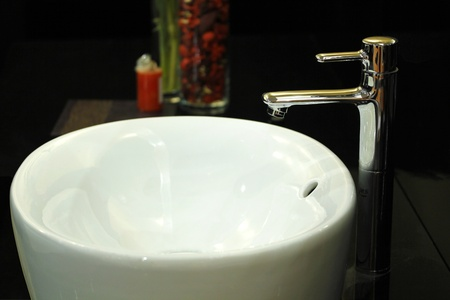 wash basin: A white wash basin with contemporary tap