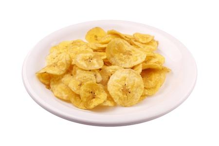platanos fritos: Chips de pl�tano en un plato y aislado en blanco