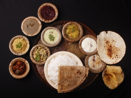 paratha: Indian lunch on stiched leaf plate and bowls made of leaves Stock Photo