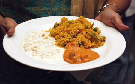 Indian traditional rice delicacy, biryani, with raitha and curry photo