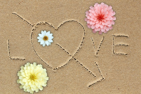Love word with love symbol and flowers on sand Stock Photo - 11513735