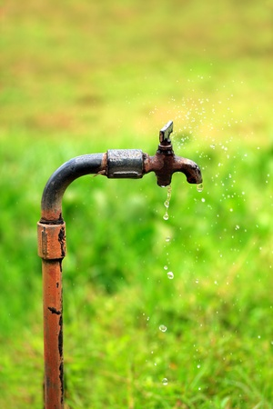 Old rusty tap with water dripping and spraying photo