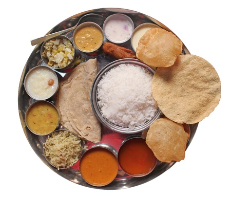 Traditional indian lunch food and meals with rice, phulka, puri, curries and sweets isolated on white photo