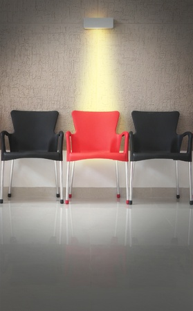limelight: Three chairs in line and light on the middle chair. Concept of being different from the rest.
