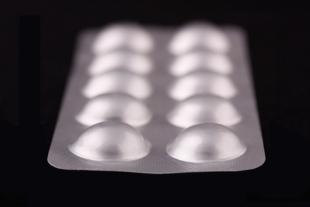 new medicine: Tablets strip macro view on a black background Stock Photo