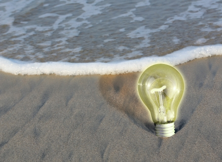Glowing ight bulb on a beach, concept of determination, persistence, staying put and remaining steady. photo