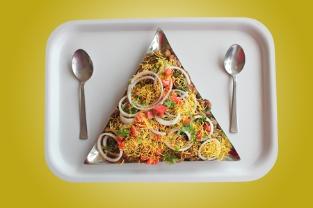 pani: Masala or sev puri - indian chaat snack made with tangy sauce, fried bread, vegetables and fruits and sev.