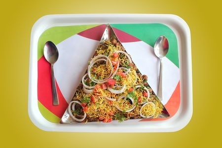 chaat: Indian chaat snack called masala puri or sev puri made with tangy sauce, fried bread, vegetables and fruits and sev.