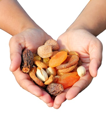 Woman holding bunch of dry fruits like almonds, raisins, dates and apricots isolated on white photo