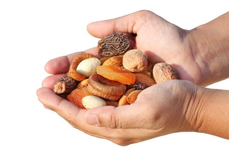 Bunch of dry fruits in a woman's hand. Dry fruits like almonds, raisins, dates and apricots isolated on white Stock Photo - 12195882