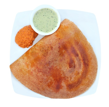 dosa: Golden masala dosa with two different chutneys on a plate isolated on white