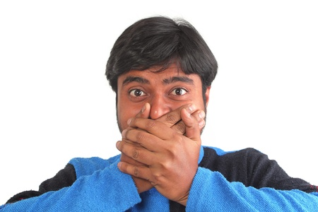 disbelief: Young south indian youth holding his mouth with hands showing facial expression of disbelief or surprise Stock Photo
