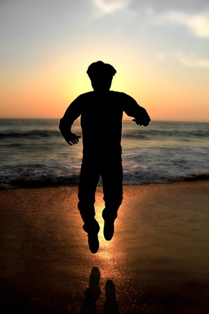 Silhouette of a young male adult jumping at evening on a beach with glowing sun and waves in the background Stock Photo - 12436157