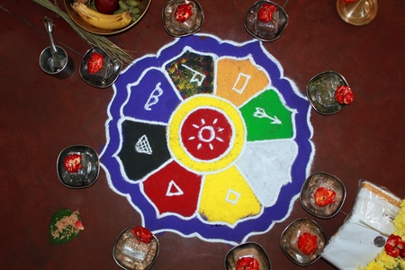 Colorful rangoli art with hindu puja items, flowers, dhoti and money
