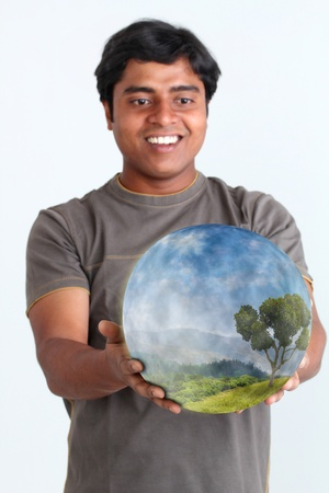 Person smiling and holding glowing ball containing ecosystem. Concept of sustainable environment. photo