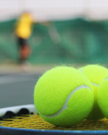 raquet: Tennis balls on racket strings with a sports person practising in the background