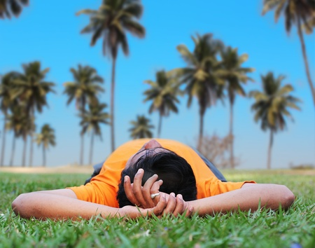 Young person relaxing in a garden on a lawn with coconut trees in the background photo