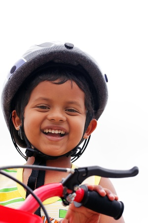 Young indian boy with helmet expressing happiness with a big smile as he rides a bike photo