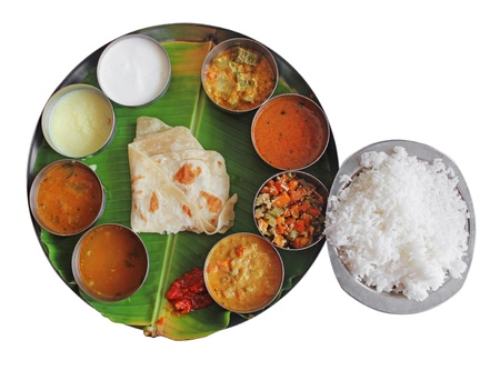 South indian plate meals on banana leaf isolated on white. Traditional vegetarian wholesome indian food with variety of curries, rasam, sambar, rice and chapatti. photo