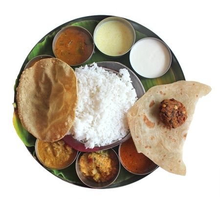 veg: Traditional southern indian plate meals on banana leaf isolated on white. Traditional vegetarian wholesome indian food with variety of curries, rasam, sambar, rice and chapatti.
