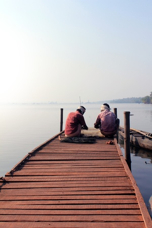 Fishermen sitting on a wooden platform with the fish catch in early moning near cherai village at kochi, kerala, India