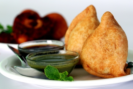 Popular indian, asian and african deep fried snack called samosa with spicy chutney and mint photo