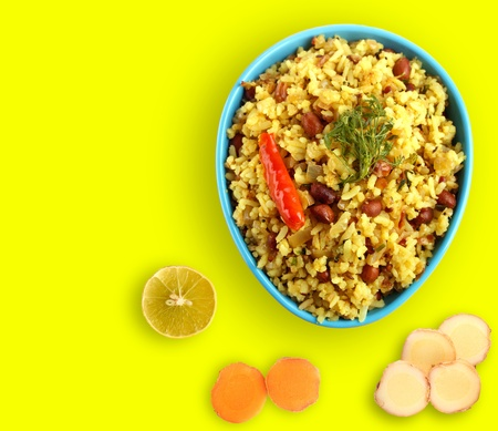 pakistani food: Spicy south indian breakfast called chitranna or poha with its ingredients - lemon, ginger and fresh turmeric. Stock Photo