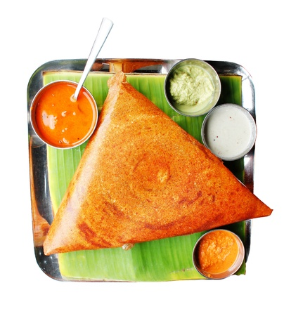 Popular south indian breakfast dosa in golden brown color with 3 types of chutney and sambar photo