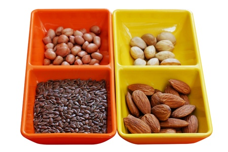 Dry fruit seeds - almond, pistachio, peanut and flaxseed in colorful containers photo