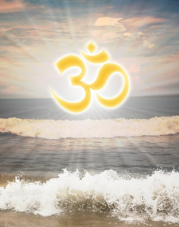 against the sun: Hindu religious symbol om or aum against sun shine in the background and waves from the ocean in the foreground