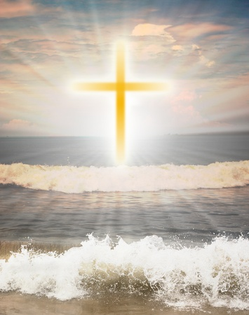Christian religious symbol cross against sun shine  in the background and waves from the ocean in the foreground photo