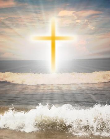 Croix chrétienne symbole religieux contre les rayons du soleil en arrière-plan et les vagues de l'océan au premier plan