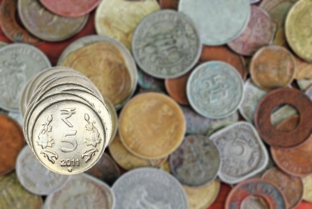 New 5 rupee coins stacked one above the other and other olad and new indian coins in the background photo