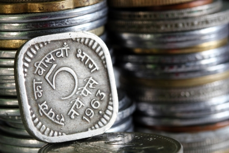 1963 printed 5 Paisa indian currency coin with stack of other coins in the background photo