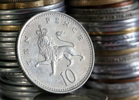 English 10 pence coin with lion symbol and stack of coins piled in the background Stock Photo - 13858902