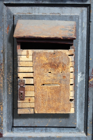 Old, grungy and vintage wooden dropbox hung on a old door photo