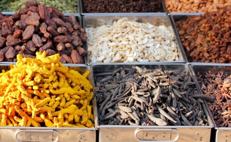 Dry fruits and spices like cashews, raisins, turmeric, cloves, anise, etc. on display in containers for sale in a bazaar in bangalore, india.  photo