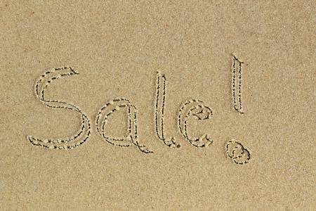 communication �crite: Main mot Vente �crit avec d'exclamation sur le sable sur une plage - un message de communication aux consommateurs sur remise sur achat